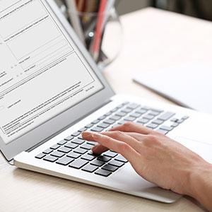 En læge, der indtaster oplysninger i elektroniske blanketter til Forsikring & Pensions